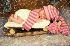 El bebé está durmiendo en trineos de madera ` S Eve del Año Nuevo Foto de archivo