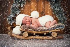 El bebé está durmiendo en trineos de madera ` S Eve del Año Nuevo Fotografía de archivo libre de regalías