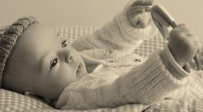 El bebé está jugando con un traqueteo Imagen de archivo libre de regalías