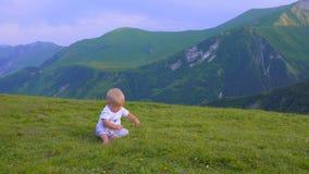 El bebé está jugando en las montañas, la sentada y la sonrisa almacen de metraje de vídeo