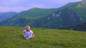 El bebé está jugando en las montañas, la sentada y la sonrisa almacen de video