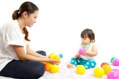 El bebé está jugando la bola con su madre imagen de archivo