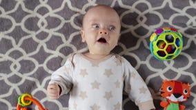 El bebé está mintiendo en el sofá con los juguetes almacen de video