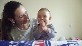 El bebé feliz aplaude las manos con la madre sonriente 4k almacen de video