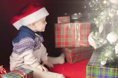 El bebé feliz cerca adornó el árbol de navidad con muchos caja de regalo Foto de archivo