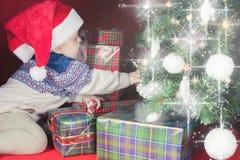 El bebé feliz cerca adornó el árbol de navidad con muchos caja de regalo Imagen de archivo libre de regalías