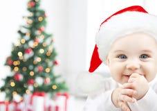 El bebé feliz en el sombrero de santa sobre el árbol de navidad se enciende Imagen de archivo