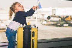 El bebé feliz lleva su equipaje en el terminal de aeropuerto Imagenes de archivo