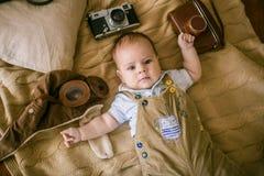 El bebé feliz miente en una manta de la casa con libros, una cámara retra y un casco experimental del ` s en casa fotografía de archivo