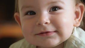 El bebé feliz que mira la cámara y que sonríe feliz, se cierra encima del retrato, niño precioso almacen de video