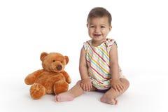 El bebé feliz se sienta además de su juguete del oso Imagenes de archivo