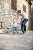 El bebé hace sus primeros pasos con ayuda de su madre Fotos de archivo libres de regalías