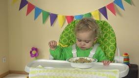 El bebé hambriento con la cuchara se sienta en la silla de alimentación y come las gachas de avena de la placa almacen de video