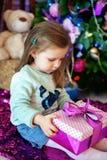 El bebé hermoso abre un regalo El concepto de la Navidad y de un happ Fotografía de archivo libre de regalías