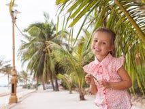 El bebé hermoso en la camisa rosada está permaneciendo cerca de la palma y de la sonrisa fotos de archivo