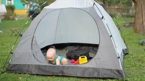 El bebé hermoso está jugando con una tienda grande en la hierba Bebé menos que un año, en una camiseta verde y juguetes dentro de metrajes