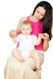 El bebé hermoso se sienta en el regazo de su madre imagen de archivo