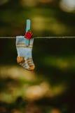 El bebé hizo punto calcetines de lana en un cordón para el lino Imagen de archivo