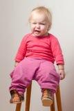 El bebé joven insatisfecho se sienta en silla Imágenes de archivo libres de regalías