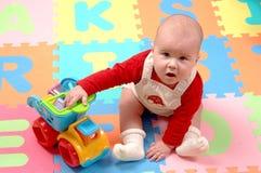 El bebé juega con el coche del juguete en los azulejos coloridos del rompecabezas Imagenes de archivo