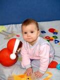 El bebé juega con un juguete del vaso de la muñeca Fotografía de archivo