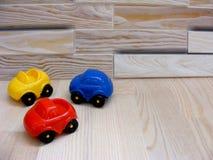 El bebé juega los coches del amarillo del rojo azul en fondo de madera imagen de archivo libre de regalías