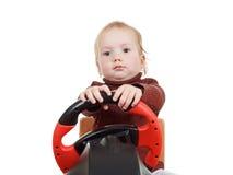 El bebé juega una videoconsola de conducción, aislada en blanco fotos de archivo libres de regalías
