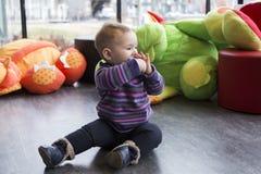 El bebé justo lindo que se sentaba en sala de juegos en mitad-perfil en piso con una pierna amplió chupar en el juguete imágenes de archivo libres de regalías