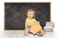 El bebé leyó el libro cerca de la pizarra, tablero del negro de la escuela del niño fotos de archivo libres de regalías