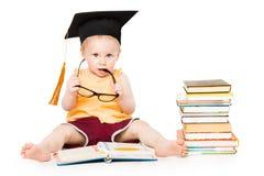 El bebé leyó el libro en el sombrero y los vidrios, niño elegante de la graduación, blanco imagen de archivo
