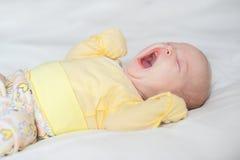 El bebé lindo bosteza en un fondo blanco Imágenes de archivo libres de regalías