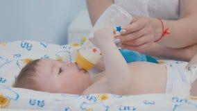 El bebé lindo come la mezcla de la botella metrajes
