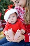 El bebé lindo con el árbol de navidad rojo y blanco del equipo en la localización del fondo en madres da mostrar pies bastante pe Imágenes de archivo libres de regalías