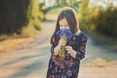 El bebé lindo con el pelo moreno y el marrón observa el retrato con las flores salvajes púrpuras azules profundas que llevan desc Foto de archivo