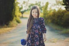 El bebé lindo con el pelo moreno y el marrón observa el retrato con las flores salvajes púrpuras azules profundas que llevan desc Imagen de archivo libre de regalías