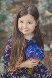 El bebé lindo con el pelo moreno y el marrón observa el retrato con las flores salvajes púrpuras azules profundas que llevan desc Fotos de archivo libres de regalías