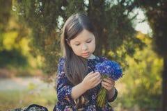 El bebé lindo con el pelo moreno y el marrón observa el retrato con las flores salvajes púrpuras azules profundas que llevan desc Fotos de archivo