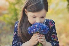 El bebé lindo con el pelo moreno y el marrón observa el retrato con las flores salvajes púrpuras azules profundas que llevan desc Imagenes de archivo