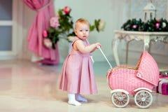 El bebé lindo en vestido rosado rueda el cochecito en el fondo de Fotografía de archivo