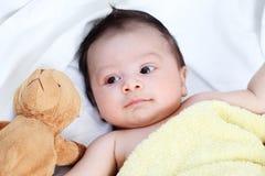 El bebé lindo es feliz con el amigo precioso amarillo del oso de la manta y de la muñeca en la cama blanca Imagen de archivo libre de regalías