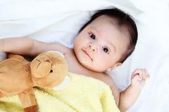 El bebé lindo es feliz con el amigo precioso amarillo del oso de la manta y de la muñeca en la cama blanca Fotos de archivo