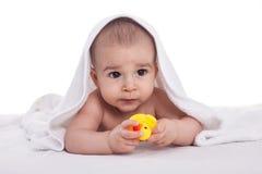 El bebé lindo goza debajo de la toalla blanca con los juguetes del baño, aislados Imagenes de archivo
