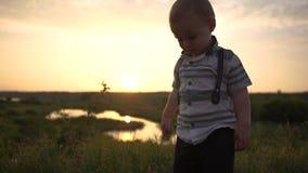 El bebé lindo lanza una pila enorme de billetes de dólar, estando en naturaleza en la puesta del sol almacen de metraje de vídeo