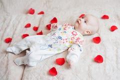 El bebé lindo miente en pétalos de la flor fotografía de archivo