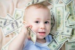 El bebé lindo que juega con mucho dinero le gusta hablar en el teléfono, americano cientos dólares de efectivo imagenes de archivo