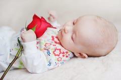 El bebé lindo que sostenía un ramo de flores subió imagen de archivo