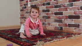 El bebé lindo se está arrastrando en piso en casa, vídeo de la cámara lenta almacen de metraje de vídeo