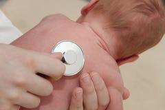 El bebé masculino consigue un examen del pulmón de una enfermera con el estetoscopio Fotografía de archivo libre de regalías