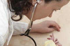 El bebé masculino consigue un examen del pulmón de una enfermera con el estetoscopio Fotos de archivo libres de regalías