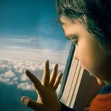 El bebé mira fuera de la ventana del airplain Imágenes de archivo libres de regalías